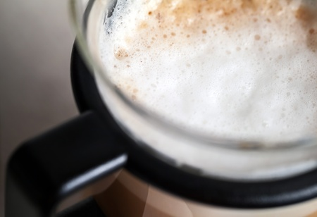 Closeup shot of milk foam on cappuccino in glass mug photo
