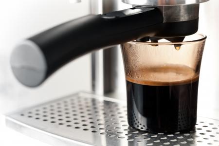 expresso: Modern glass of black coffee with espresso machine Stock Photo