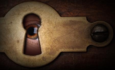 Bruine ogen kijken door een vintage metalen sleutelgat