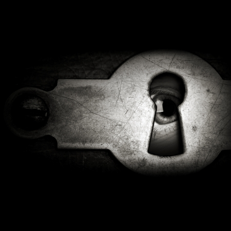 peep: Eye looking through a vintage metal keyhole in the dark Stock Photo