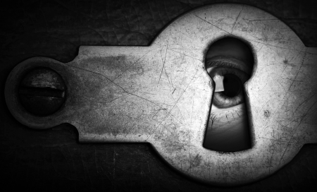 Eye looking through an old dark metal keyhole\