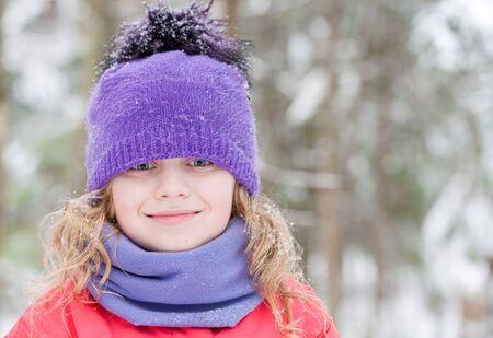 outwear: Little beautiful blond girl in winter outwear with snowflakes above forest background Stock Photo
