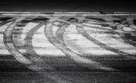 track marks: Turning wet tire tracks and line marking on the asphalt road Stock Photo