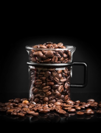caffee: Mug made of glass with roasted coffee beans on black background