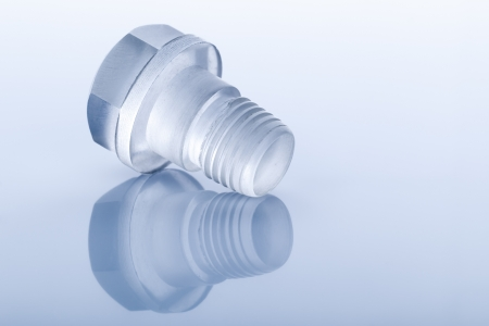 Unusual Bolt made of transparent plastic on light blue background with reflection