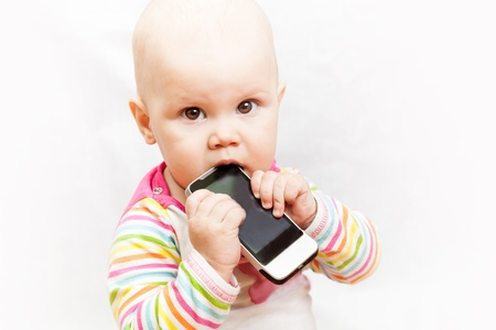 little baby baby chews on a mobile phone in colorful clothing Stock Photo - 17658864