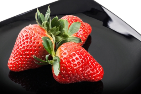 Three fresh strawberries on black saucer photo