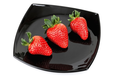Three fresh strawberries on black saucer isolated on white photo