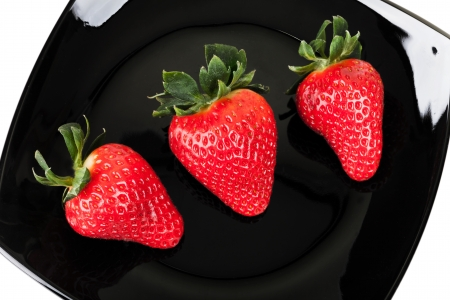Three fresh strawberries on black saucer, top view photo