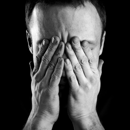 desperate: Monochrome portrait of young stressed Caucasian man covers his face with hands isolated on black background