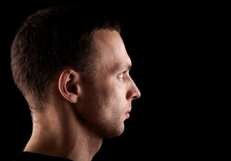 Profile portrait of serious young Caucasian man isolated on black background photo