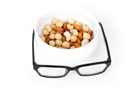 mixed nuts: Mental pabulum concept  Mixed nuts in white pot with black glasses as a food for brain