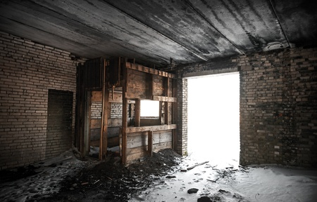 Old grunge abandoned barn interior with glowing exit photo