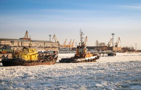 tug boat: Small tug boat goes with vessel through icy channel in harbor of St Petersburg cargo port Editorial
