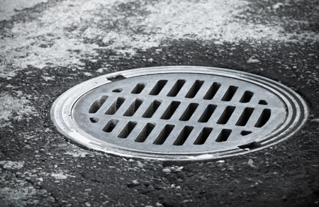 Sewer manhole on the urban asphalt road  Closeup photo photo