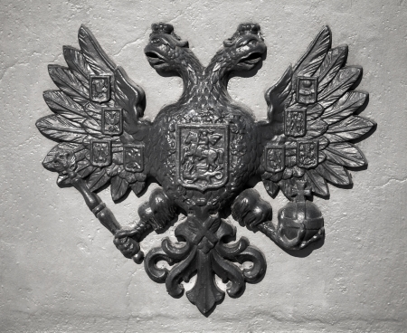 double headed: Double Eagle - Emblem of Russia  Ancient black bas-relief on gray vintage wall Editorial