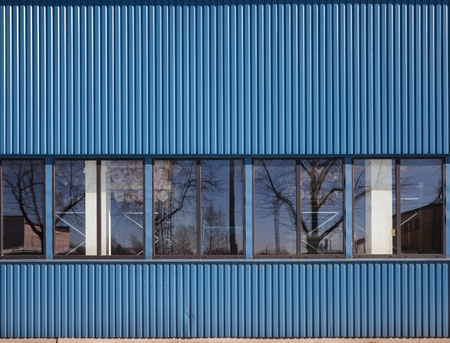 Texture of industrial storage building with windows on metal ridged blue wall photo