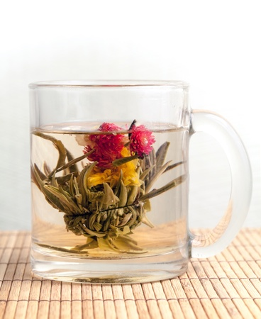 Green Chinese flower tea is brewed in the cup on bamboo carpet Stock Photo - 18789607