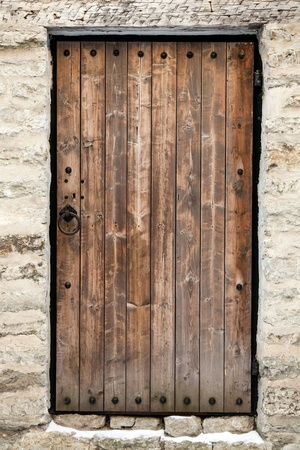 Ancient wooden door in old stone castle wall. Tallinn, Estonia photo