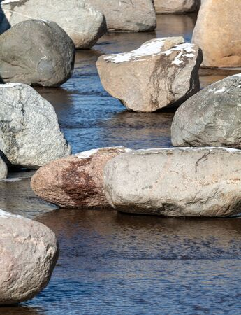 Stones with snow in shallow spring stream photo