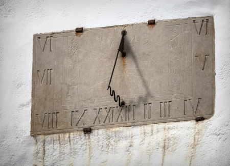 Ancient sundial with signs of the zodiac on white church wall in Tallinn, Estonia photo