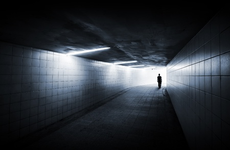 Man goes on underground passage with neon lights and glowing end