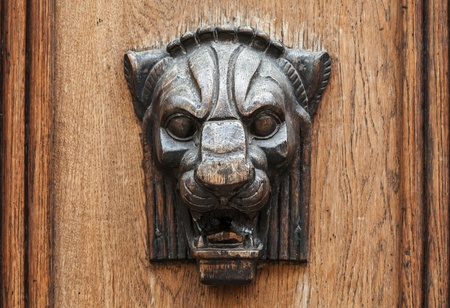 heads old building facade: Wooden lion head relief - decorative element on ancient weathered door  in old part of Tallinn, Estonia