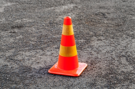 Red and yellow striped warning cone on asphalt road photo