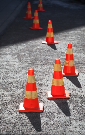 danger symbol: Red and yellow striped warning cones in line on asphalt road