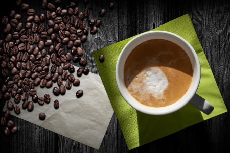 Cup of cappuccino coffee, old paper sheet, green napkin and beans on black wooden table, top view photo