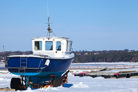 Small blue boat on the snowy coast of Baltic Sea in winter photo