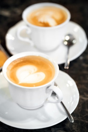 Two white cups of Cappuccino with heart shaped milk foam  Selective focus photo