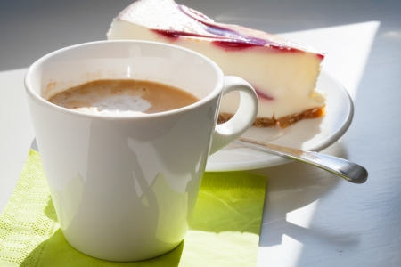 Cup of cappuccino coffee and cheesecake piece on white table  Selective focus photo