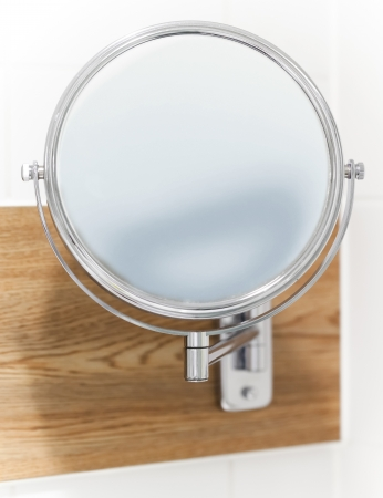 wall mirror: Round wall mirror for the bath. Close-up photo with selective focus