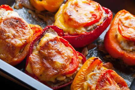 Stuffed bell peppers on black baking pan photo