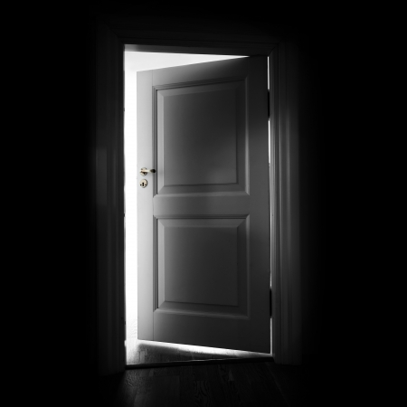 Opening white door in a dark room with light outside photo