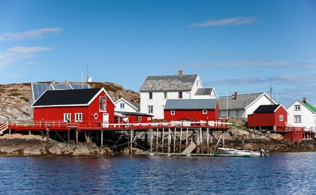 Traditional Norwegian village with red and white wooden houses on rocky coast photo