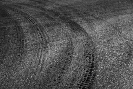squeal: Dangerous turn  Abstract road background with tires tracks on dark asphalt Stock Photo