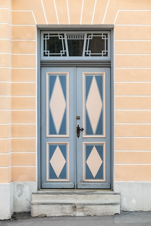 Blue wooden door with decor in old building facade  Tallinn, Estonia photo