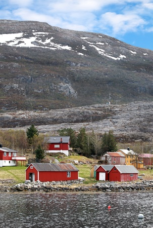 Traditional small Norwegian village with red wooden houses on rocky coast with mountains on the horizon photo