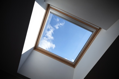 Looking up to the blue cloudy sky through modern square ceiling window photo