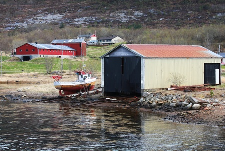 Traditional Norwegian wooden barns and small fishing boat on the sea coast photo