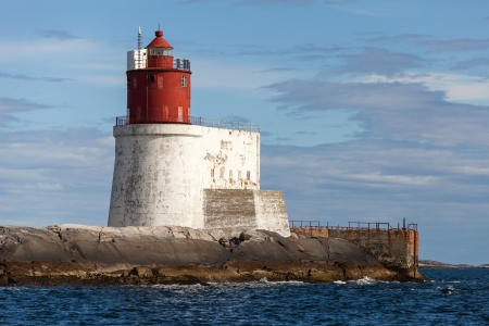 Gjeslingene  Norwegian Lighthouse with White Base and Red Tower on Rocky Island photo