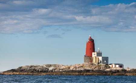 Grinna  Red Norwegian Lighthouse with Large Red Tower on Rocky Island   It was established in 1904 and automated in 1987 photo