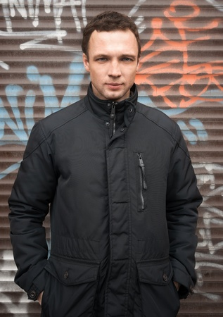 Portrait of young Caucasian man in black jacket with graffiti on a background photo