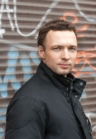 Portrait of young Caucasian man in black with graffiti on a background photo