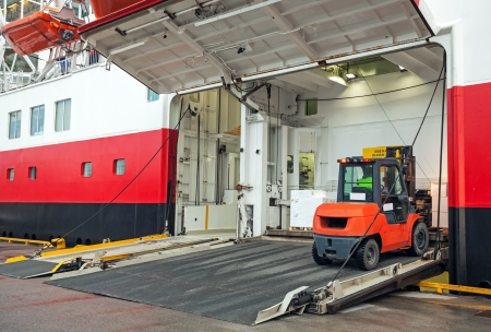 Lift truck unloads big passenger ferry through opened side ramp photo