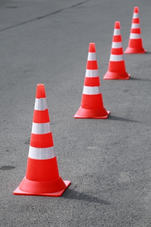 Four striped orange cones stand on gray asphalt road photo