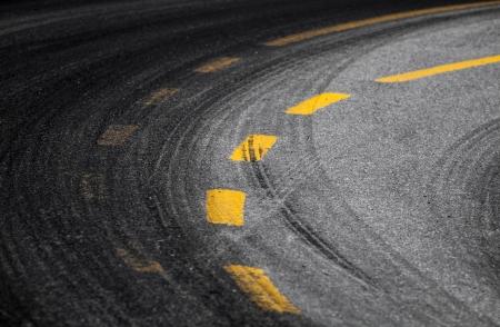 Abstracte draaien weg achtergrond met banden spoor en geel gestreepte wegmarkering op donkere asfalt