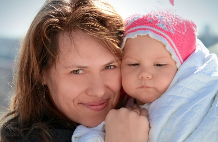 Young European woman holds her sleepy baby girl in blanket photo